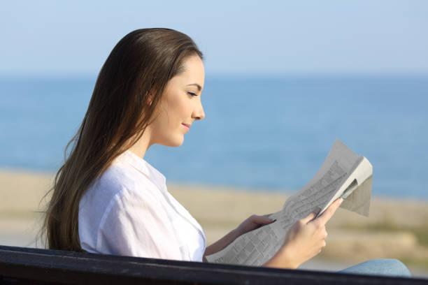 vrouw, lezen een krant buiten op het strand - newspaper beach stockfoto's en -beelden