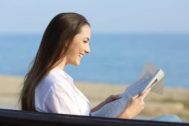 vrouw, lezen een krant zittend op een bankje op het strand - newspaper beach stockfoto's en -beelden