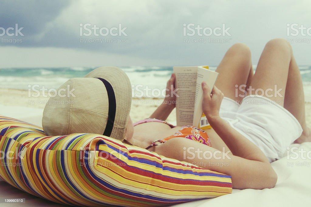 Woman reading a novel on the beach royalty-free stock photo
