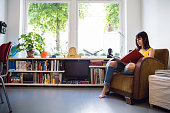 Woman reading an arts book in her beautiful house