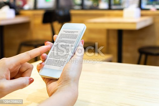 Woman reading an e-book online digital smartphone with application mobile device