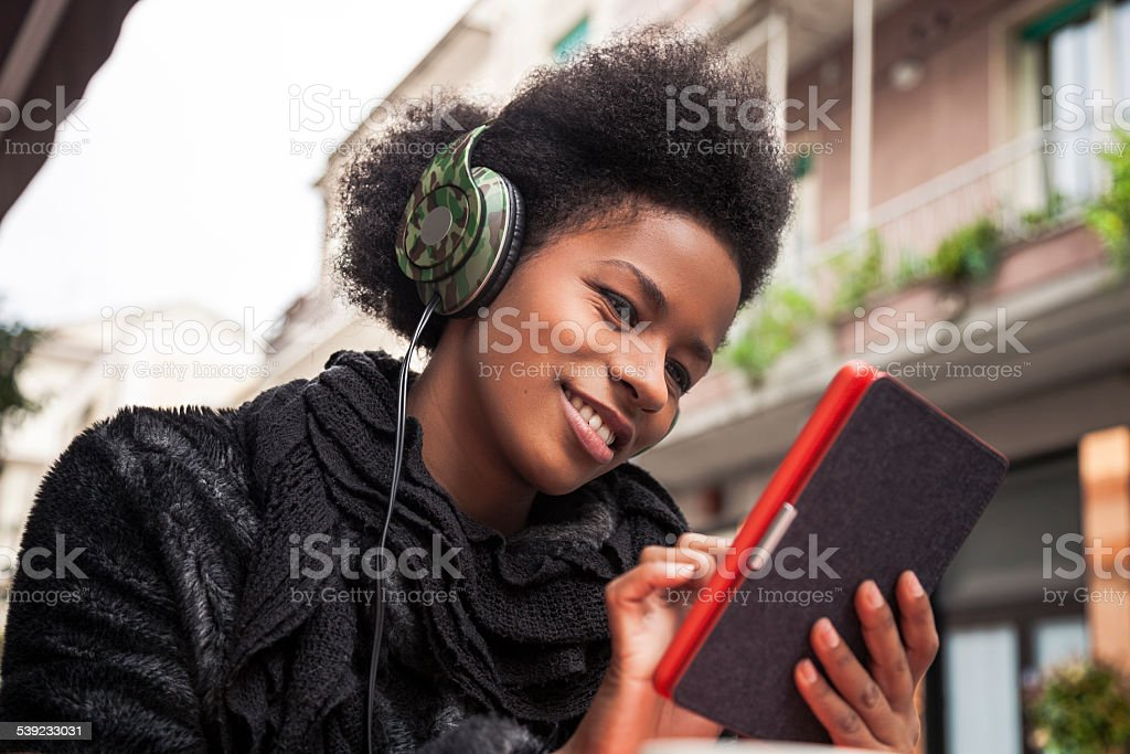 Woman reading an e-book seated on a cafe royalty-free stock photo