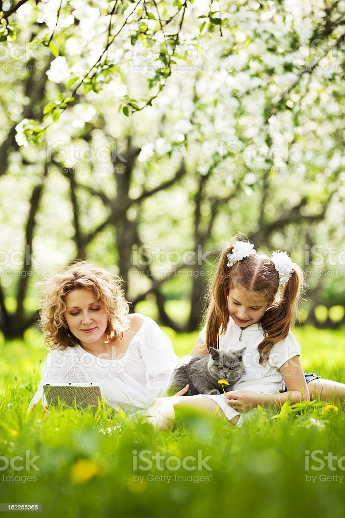 Woman reading and young girl with cat outdoors in the grass royalty-free stock photo