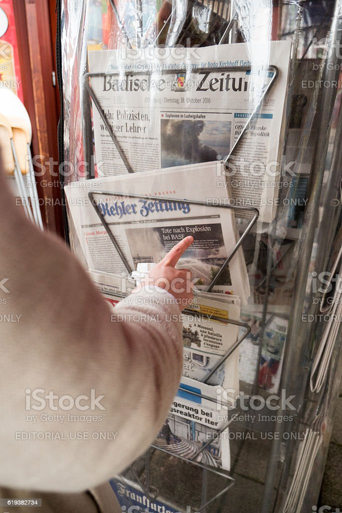 Woman reading at press kiosk about BASF explosion at Ludwigshafe – Foto