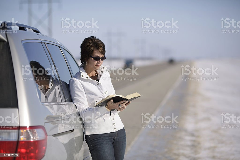 Woman reading bible on road royalty-free stock photo