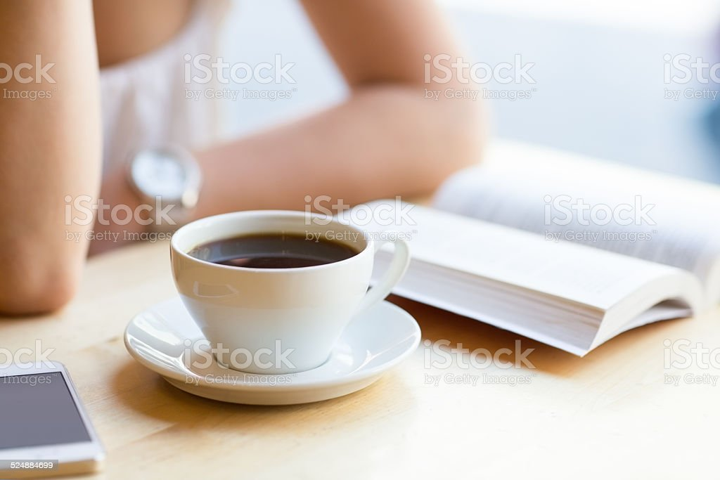 Woman reading book and drinking coffee at cafe stock photo