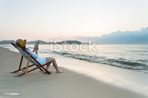 Woman reading book at the beach.