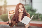 woman reading book by eating lunch