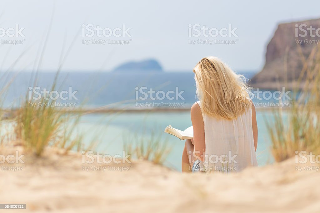 Woman reading book, enjoying sun on beach. stock photo
