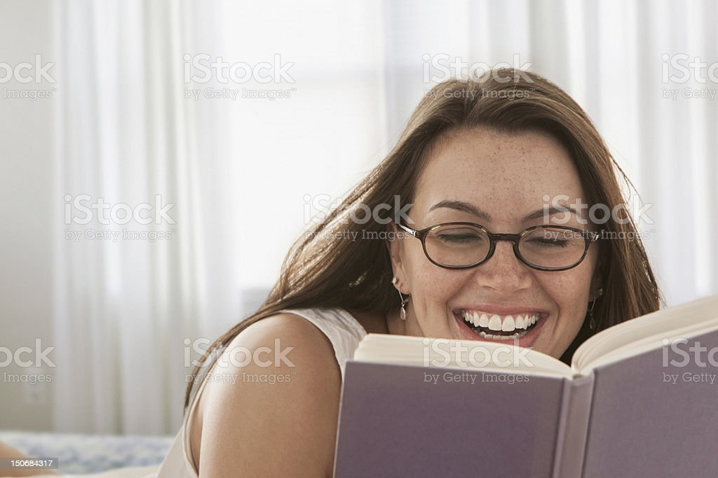 Woman reading book in bed royalty-free stock photo