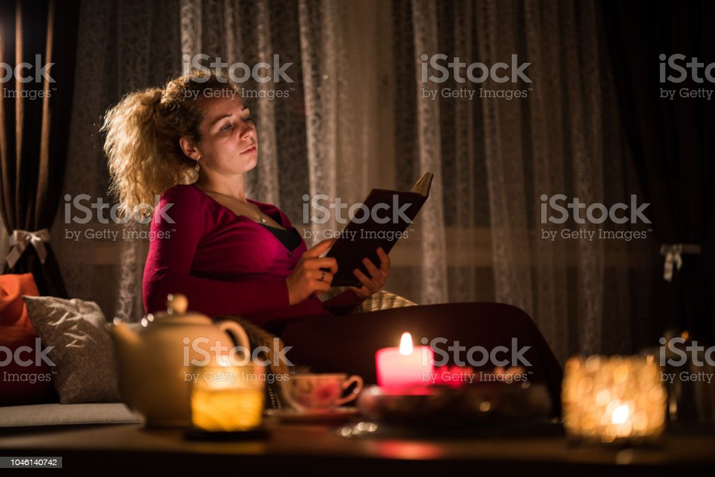 Beautiful female relaxing whit book in house at winter night.