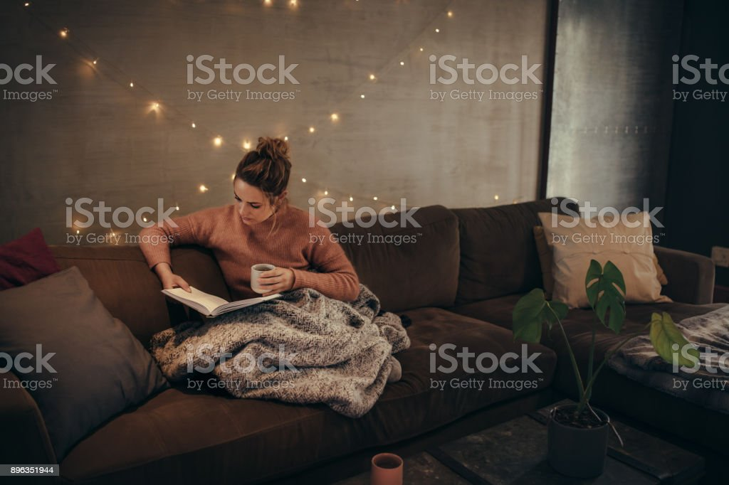 Young woman reading book and drinking coffee on sofa in hygge house....