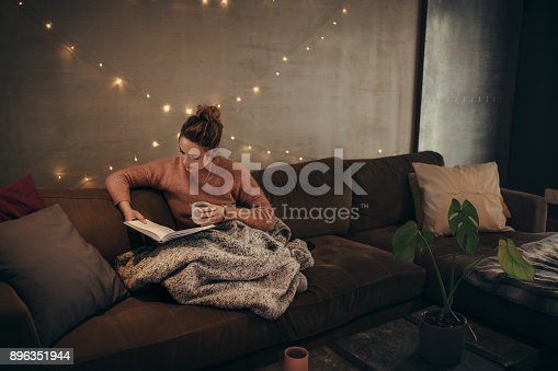istock Woman reading book in cozy living room 896351944