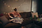 Young woman reading book and drinking coffee on sofa in hygge house. Caucasian female relaxing in cozy living room and reading a book.