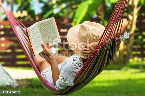 Woman reading book in hammock in tropical garden