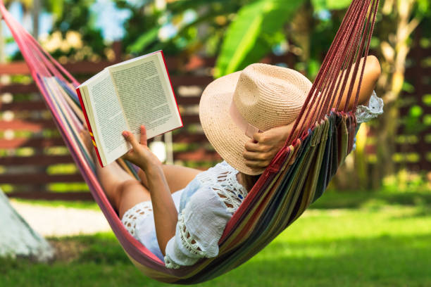 Woman reading book in hammock Woman reading book in hammock in tropical garden relaxation stock pictures, royalty-free photos & images