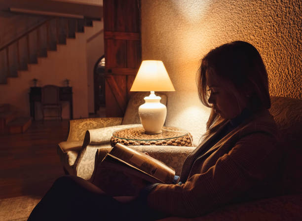woman reading book in hotel lobby at night with low light - low lighting stock photos and pictures