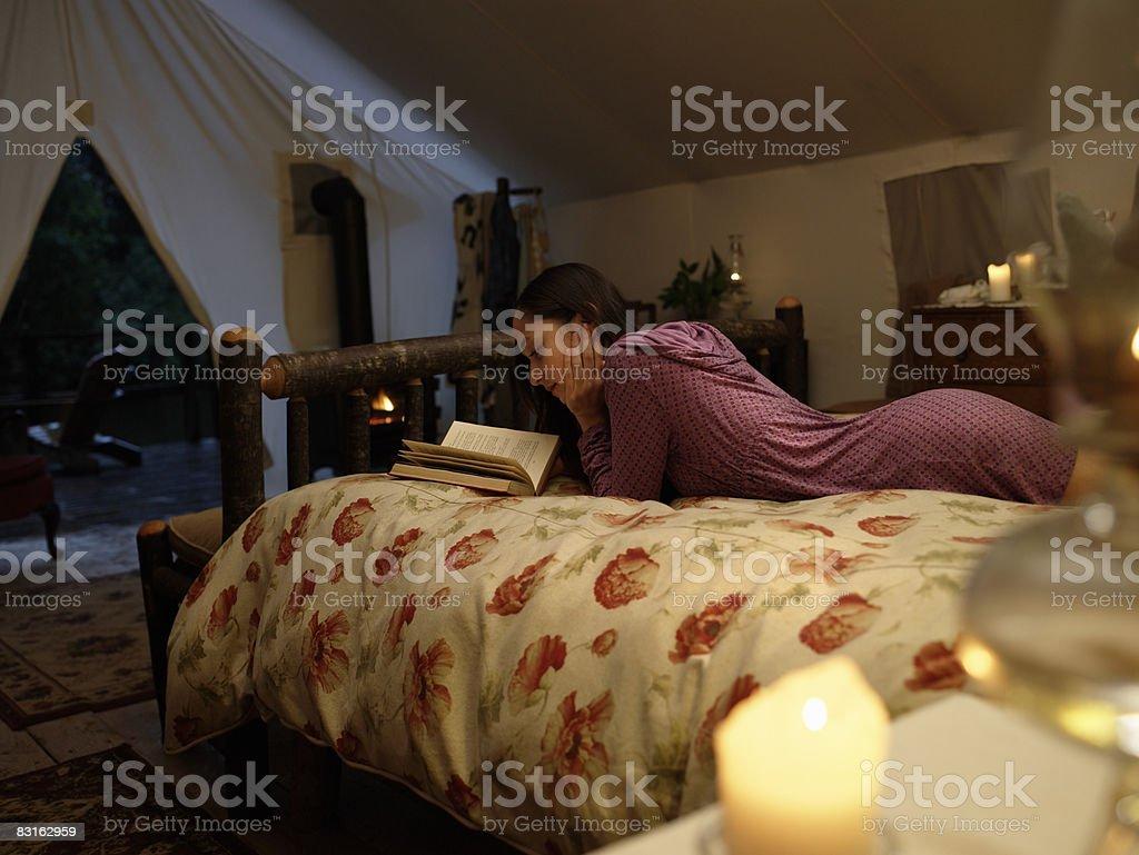 Kobieta czytanie książki na łóżku wewnątrz Namiot. zbiór zdjęć royalty-free