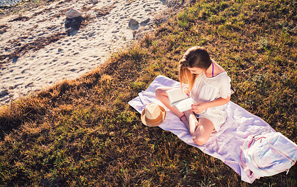 woman reading book on grass stock photo