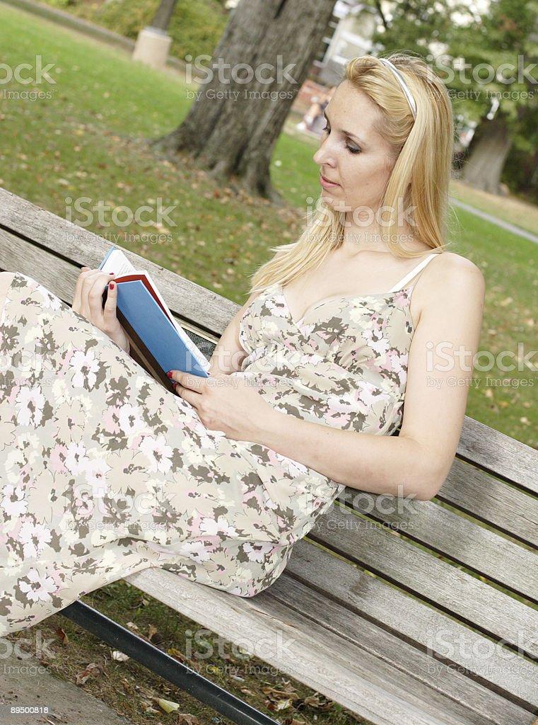 Donna lettura libro sulla Panchina pubblica foto stock royalty-free