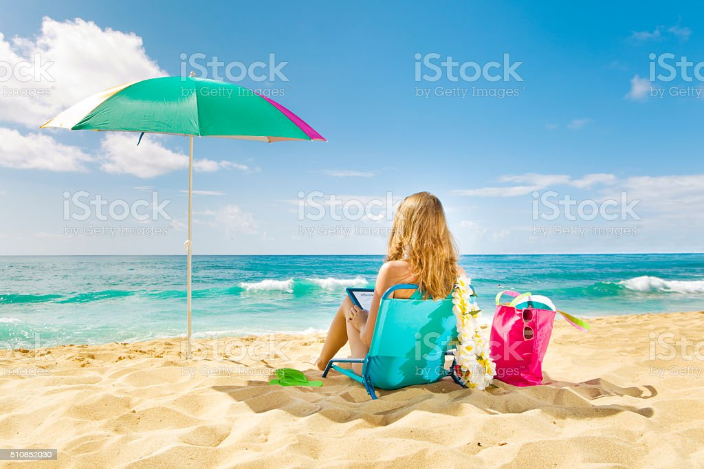 woman reading book on summer beach vacation relaxing in hawaii stock