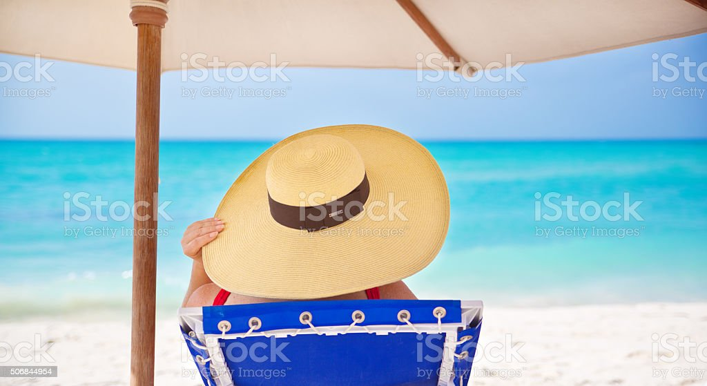 Woman Reading Book on Summer Beach Vacation, Relaxing in Mexico stock photo