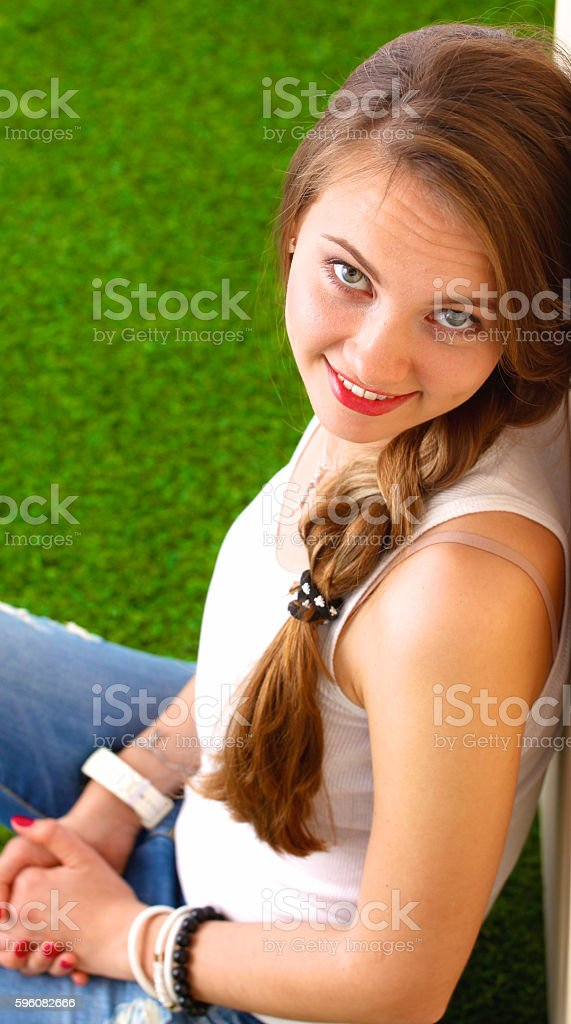 Woman reading book sits on the green grass royalty-free stock photo