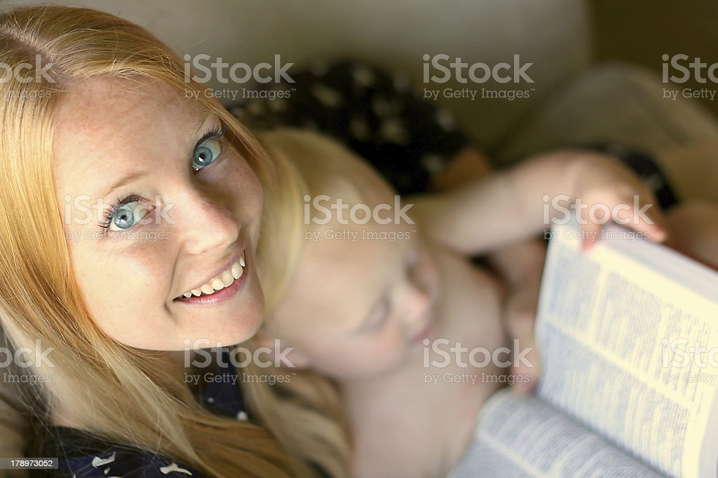Woman Reading Book While Holding Baby stock photo