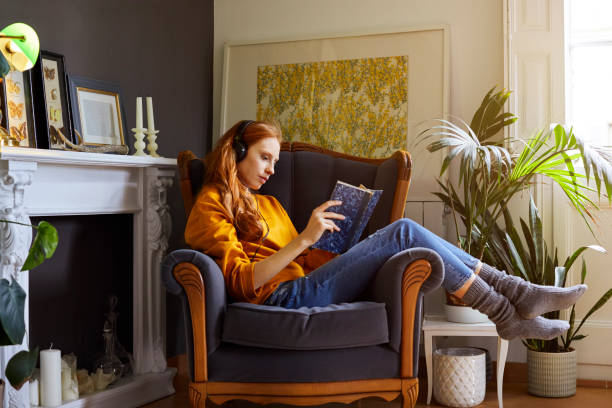 Woman reading book while listening to music Full length of young woman reading book while listening to music. Side view female is resting on chair at home. She is wearing casuals. armchair stock pictures, royalty-free photos & images