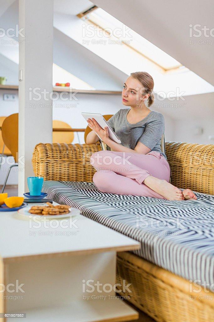 Woman reading digital tablet on sofa foto stock royalty-free