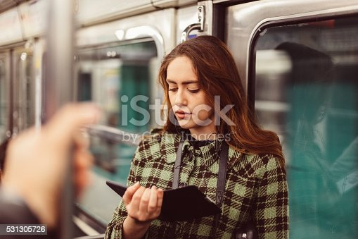 Girl reading e-book while travelling in the subway