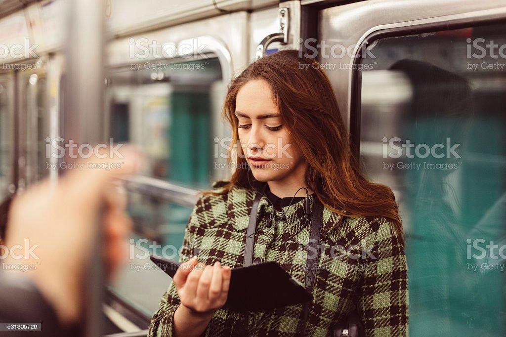 Woman reading e-book in the subway stock photo