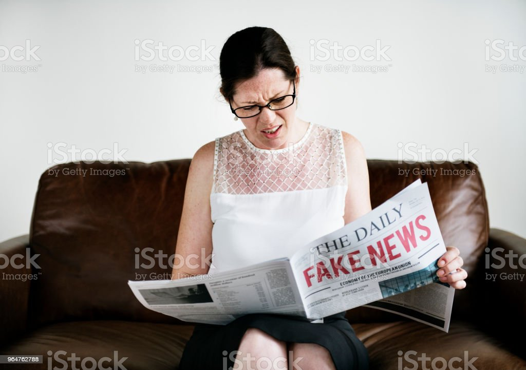 A woman reading fake news royalty-free stock photo