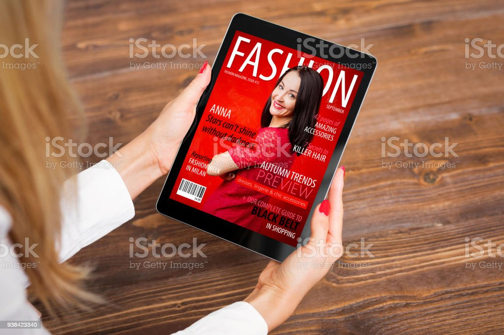 Woman reading fashion magazine on tablet stock photo