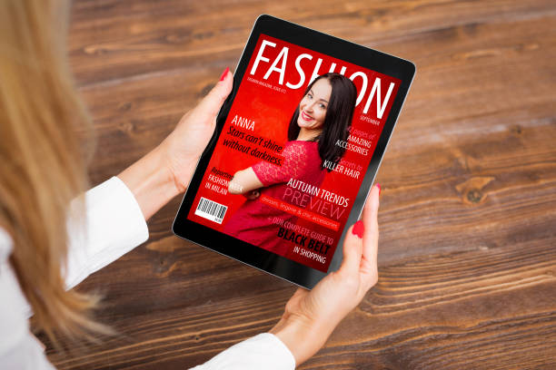 woman reading fashion magazine on tablet - magazine cover stock photos and pictures