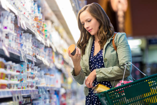 woman reading food labels at grocery store - label stock pictures, royalty-free photos & images