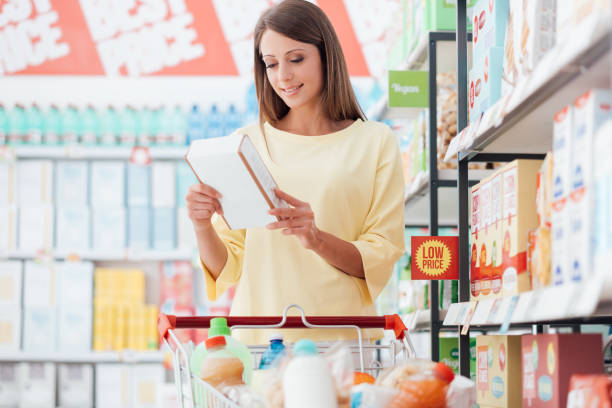 Woman reading food labels Young woman doing grocery shopping at the supermarket and reading food labels with ingredients on a box, shopping and nutrition concept discount store stock pictures, royalty-free photos & images