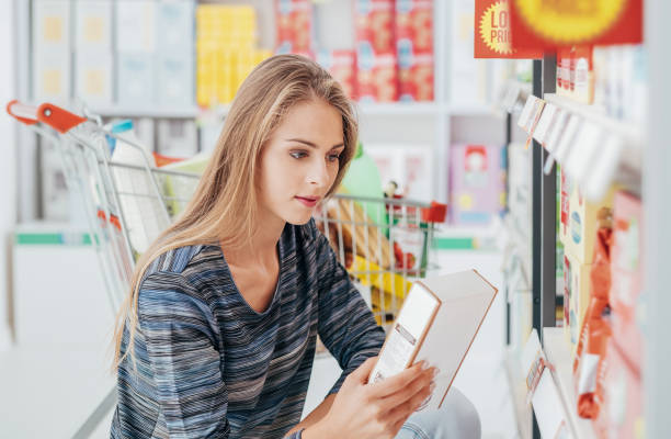 Woman reading food labels Young woman doing grocery shopping at the supermarket and reading a food label with ingredients on a box, shopping and nutrition concept discount store stock pictures, royalty-free photos & images