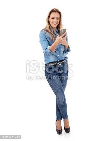 istock Woman reading good news on the phone 1126771741