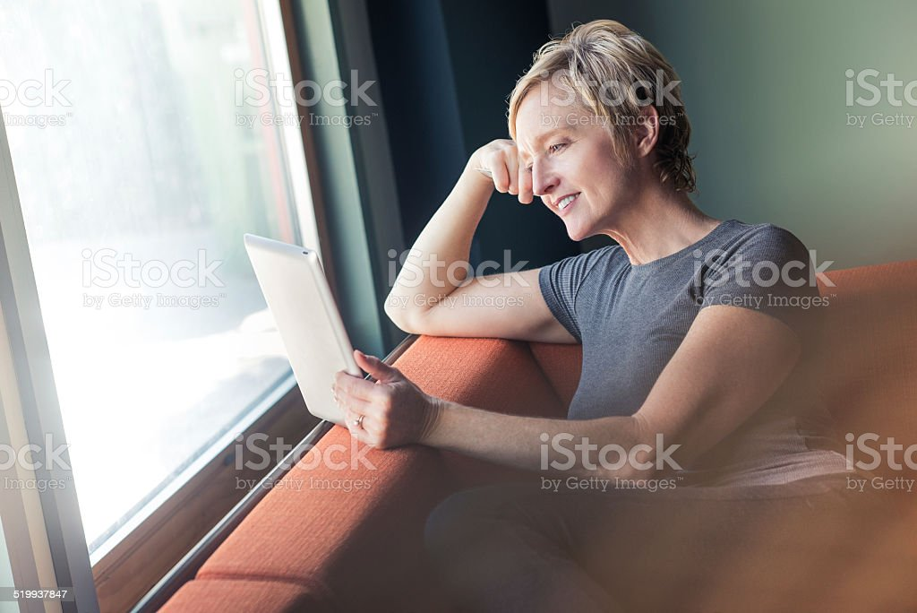 Woman Reading Her Digital Tablet stock photo