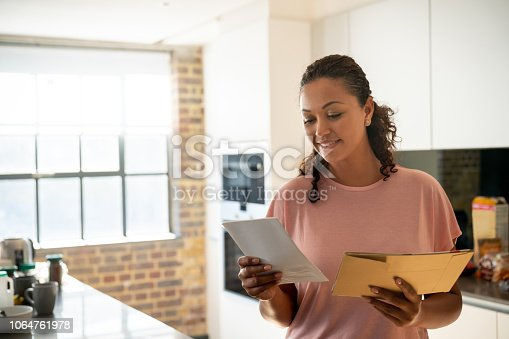 Portrait of a happy woman reading her mail at home and smiling – lifestyle concepts