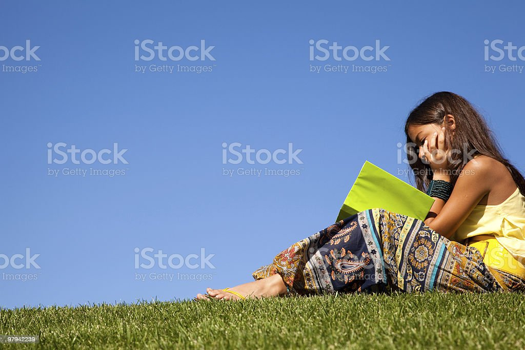 A woman reading her notes on the grass royalty-free stock photo