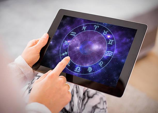 Woman reading horoscopes on tablet – Foto