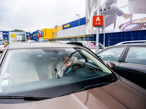 frau liest ikea katalog in auto bei ikea parkplatz - ikea schlafzimmerdesign stock-fotos und bilder