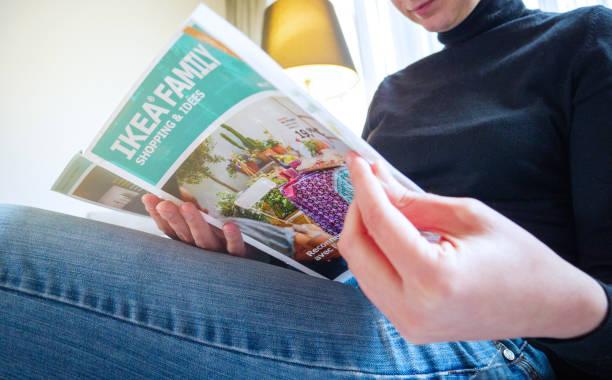 frau liest ikea katalog auf der couch im wohnzimmer - ikea couch stock-fotos und bilder