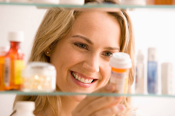 Woman reading instruction of a bottle of medicine stock photo