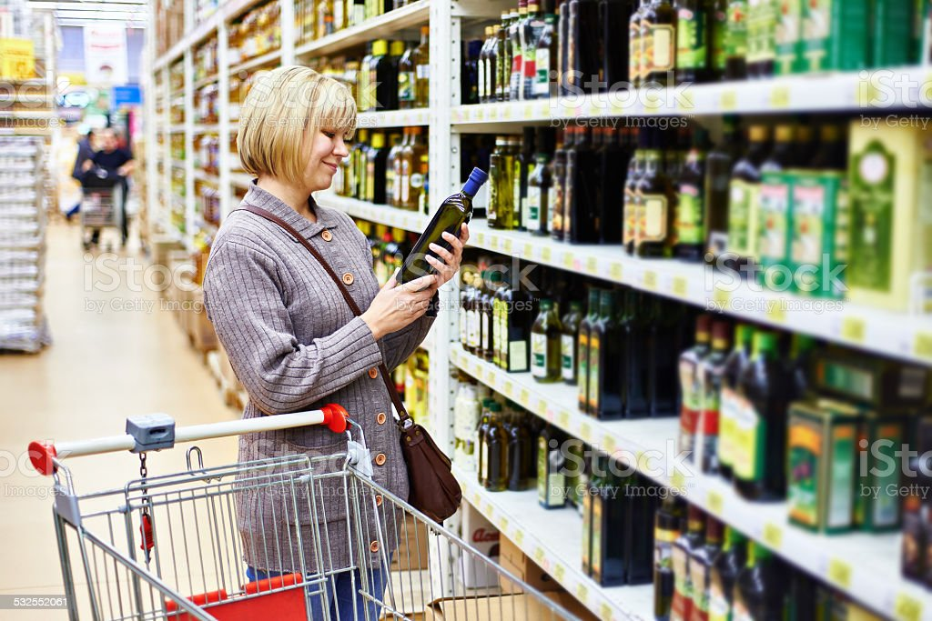 Woman reading label on bottle of olive oil in store stock photo