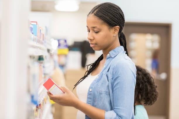 frau liest label auf über den ladentisch medikamente - lieblingsrezepte stock-fotos und bilder