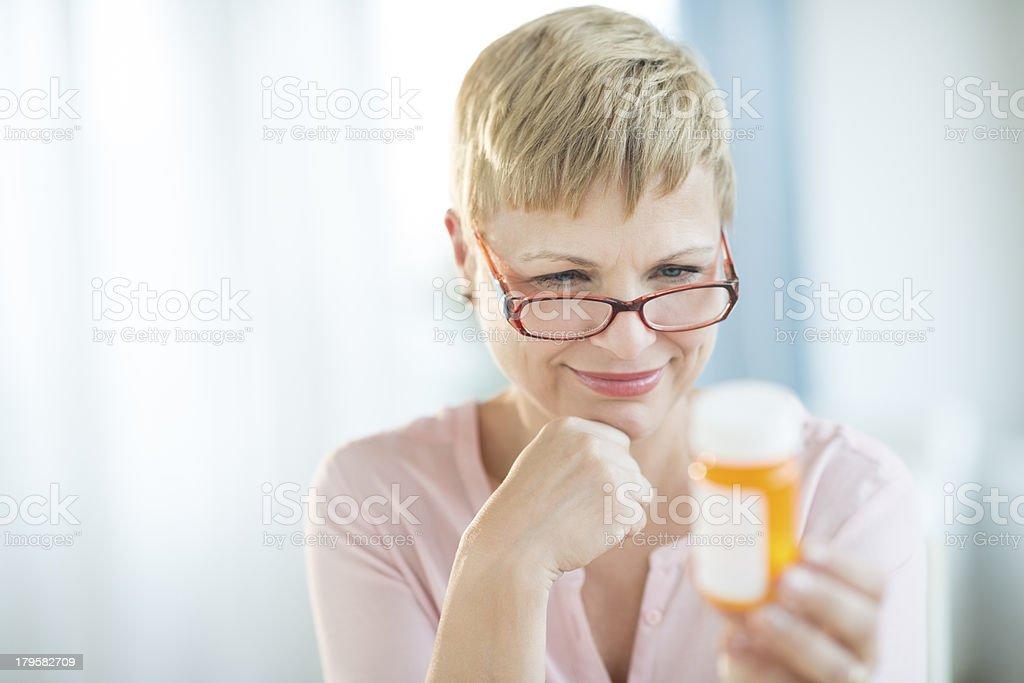 Mujer leyendo etiqueta en recipiente para las píldoras - foto de stock