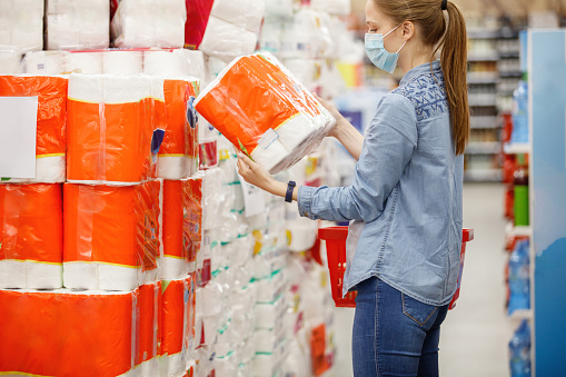 Young woman wearing protective face mask panic buying toilet paper during covid-19 pandemic, reading label on it, copy space